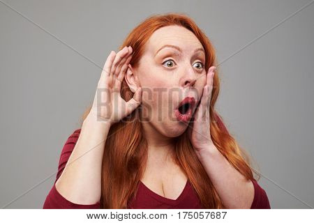Close-up of amazed young woman eavesdropping with hand to ear isolated over gray background