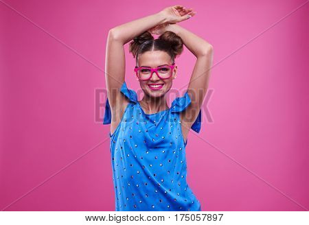 Mid shot of casual sensual young woman in pink glasses with joined hands over head. Pretty girl in dotted dress posing in studio