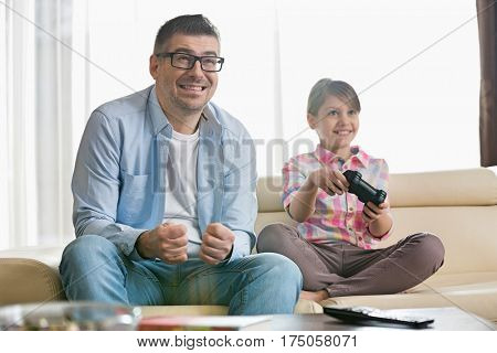 Happy father and daughter enjoying video game in living room