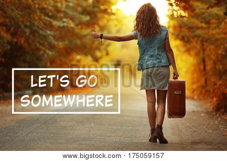 Young woman with suitcase hitchhiking on road and text LET'S GO SOMEWHERE on background