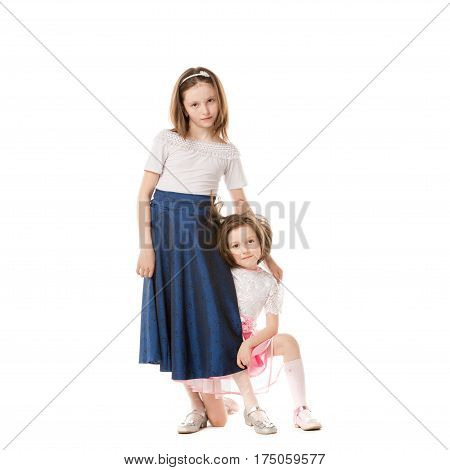 Two happy sisters in holiday dresses. Isolated over white background