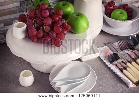 Composition with rustic dinnerware and fruits on light table