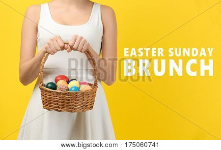 Text EASTER SUNDAY BRUNCH and woman holding basket with colorful eggs on yellow background