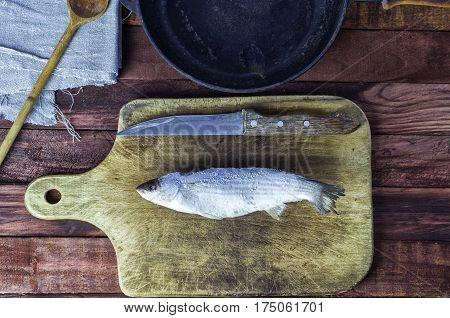 Frozen fish smelt on the kitchen board top view