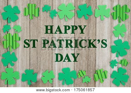 Saint Patrick's Day greeting Green shamrocks on weathered wood with text Happy Saint Patrick's Day