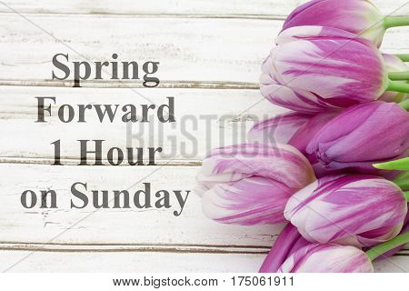 Spring Forward message A bouquet of purple tulips on weathered wood with text Spring Forward 1 hour on Sunday