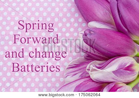 Spring Forward message A bouquet of purple tulips on pink polka dots with text Spring Forward and change Batteries