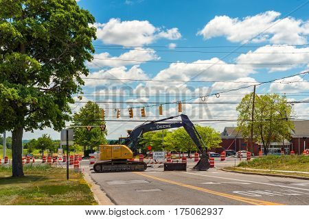 TWINSBURG OH - JULY 10 2016: A parked backhoe blocks access to an intersection in which a new roundabout is in initial stages of construction.