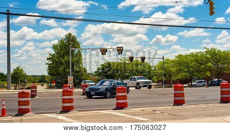 TWINSBURG OH - JULY 10 2016: Vehicles enter a partially closed intersection in which a new roundabout is in the initial stages of construction.