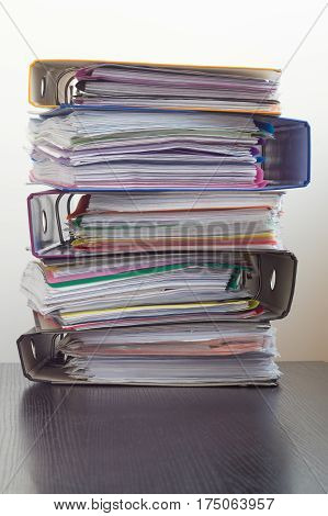 Five folders with documents stacked in a pile on the table. White background