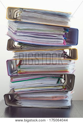 Seven folders with documents stacked in a pile on the table