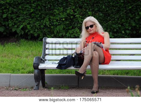 MOSCOW RUSSIA - MAY 31 2015: Mature woman in red short dress sits on the bench and reads a magazine in Gorky park