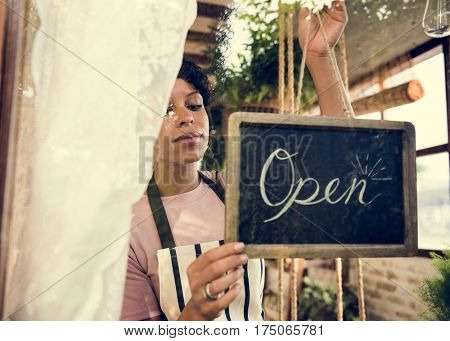 Woman Hanging Open Sign by the Glass Window poster