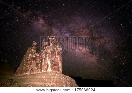Milky Way over rocks. The Three Gossips tower in Arches National Park. Moab. Utah. United States.