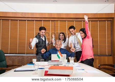 Indian business people enjoying success in conference room, either stock market or cricket or sports victory celebration in office