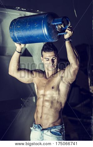 Muscular man shirtless, carrying blue gas tank above his head, wearing only jeans