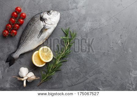 Fresh dorado or gilthead bream cooking with rosemary, cherry tomatoes, garlic and lemon on stone background