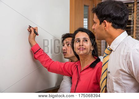 indian young businesswoman writing over white board with marker pen and other businesspeople looking