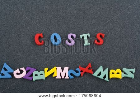 costs word on black board background composed from colorful abc alphabet block wooden letters copy space for ad text. Learning english concept