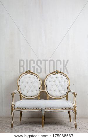 Old antique armchair furniture against grungy wall