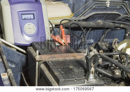 Battery charger charging the battery of an old vehicle