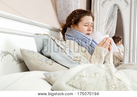 Sneezing beauty. Young sick woman with blue scarf on her neck sitting in bed and sneezing on her bed.