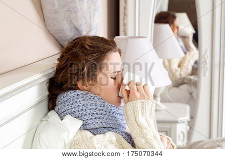 Sick woman with cup of tea. Closeup image of young frustrated woman in knitted blue scarf holding and drinking a cup of tea while sitting in bed of her room.
