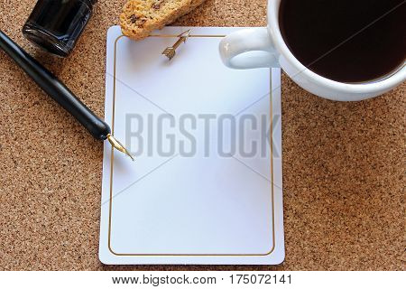 Bulletin board with pen, ink, biscotti, coffee and blank paper with arrow thumbtack.
