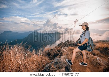 Vintage style hiker young woman happy with camera and backpack looking beautiful landscape nature of mountain in Phu Chi Fa Forest Park Chiang Rai Thailand on Sienna-Blue color two tone