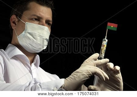 Young Man As A Doctor Gives A Medical Injection To Burkina Faso Flag On A Black Background