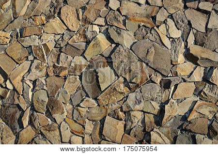 Fragment of decorative brown rough stone wall