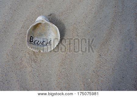 Believe Written on a Seashell in the Sand