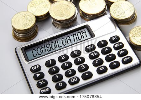 few stacks of coins and calculator with text on screen consolidation