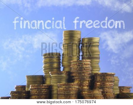 Many piles of coins against  blue sky with text financial freedom