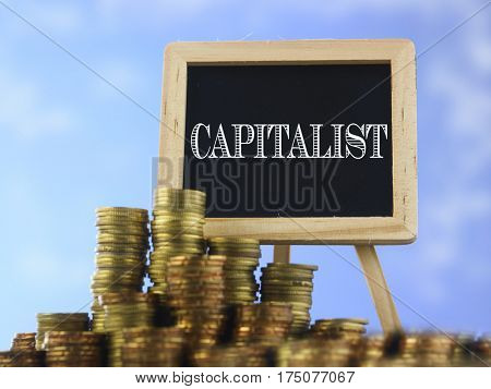 Many piles of coins against  blue sky and mini blackboard with text capital