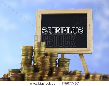 Many piles of coins against  blue sky and mini blackboard with text surplus