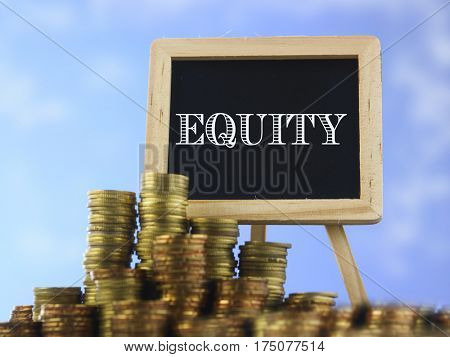 Many piles of coins against  blue sky and mini blackboard with text equity