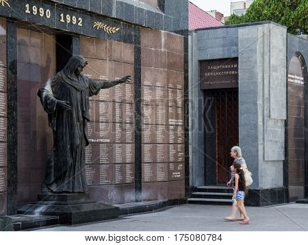 TIRASPOL TRANSNITRIA (MOLDOVA) - AUGUST 12 2016: Old woman and her granddaughter mourning in front of a monument erected to commemorate the 1992 Transnitria civil war