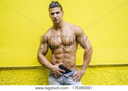 Menacing, muscular young man shirtless holding a handgun in his hand, outdoor