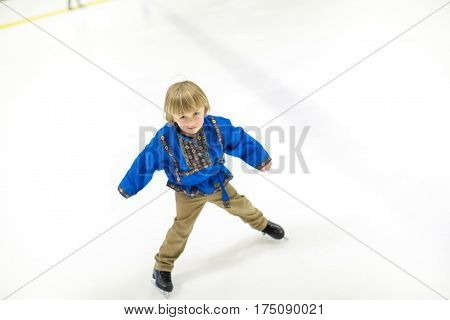 Little boy learning how to skate on indoor ice skating rink.