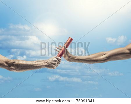 Handing off the baton in a track and field event. Focus on the exchange of the baton from one hand to another