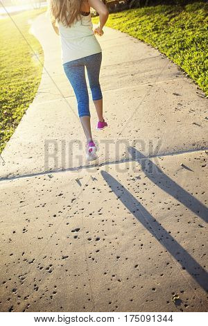 Female jogging in a city park view from behind. Beautiful blonde woman running along a city park pathway on a sunny evening outdoors. View of her legs from behind as she runs. Sun flare and bright sun