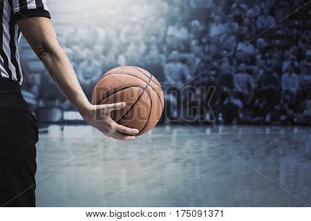 Basketball referee holding a basketball at a game in a crowded sports arena. Holding the ball in his hand during a timeout. Selective focus on the ball.