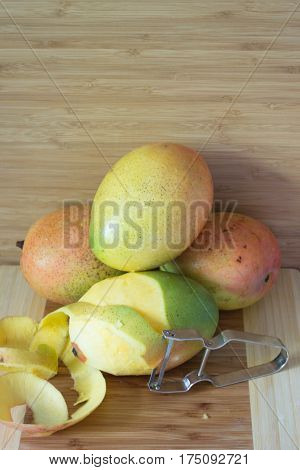 Several mangoes on wooden cutting board with peeler