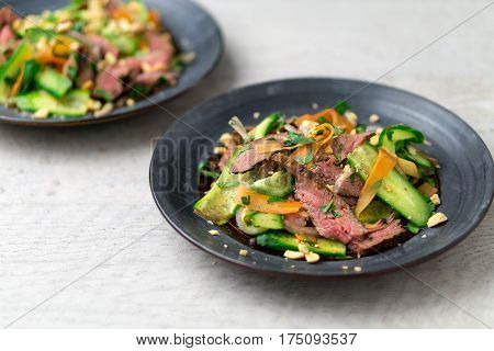Healthy asian beef salad. Angled view of 2 plates of asian beef salad. Inspired by Thai and Vietnamese cuisine this salad is made with fresh healthy vegetables (carrots onions cucumber etc) and a nicely seared flank steak.