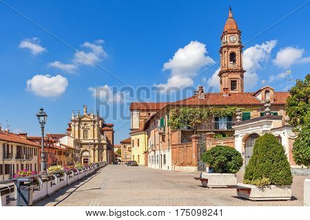 Promenade along old colorful houses and church under blue sky in town of Bra in Piedmont, Northern Italy.