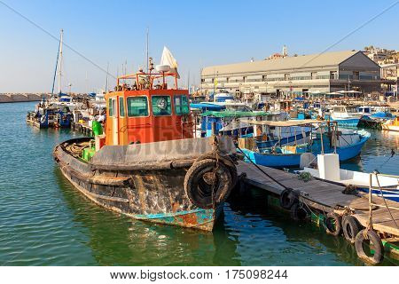 Old colorful rust fisherman boat tied to a pier in port of old Jaffa in Israel.