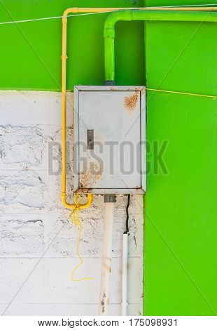 Rusty Iron Control Box on White and Green Concrete Wall