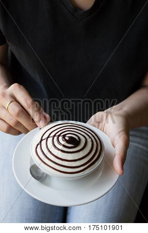 Woman Hand On White Cup Of Banoffee Pie stock photo