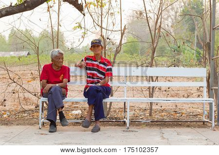 CHIANG RAI THAILAND - FEBRUARY 19 : Unidentified asian man suffering from leprosy sitting on wood chesterfield on February 19 2016 in Chiang rai Thailand.